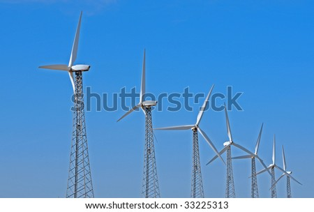 horizontal of a row of wind turbines against a blue sky