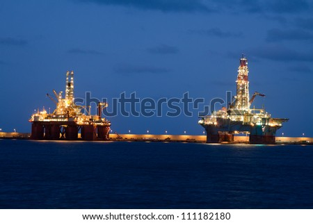 horizontal oil drilling platforms at night in Canary Islands - stock photo