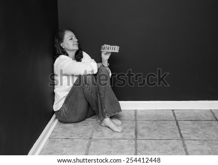 horizontal orientation black and white image of an attractive, smiling, woman, sitting on the floor, in the corner of a dark room, with a pill box / Improvement through Medication - stock photo