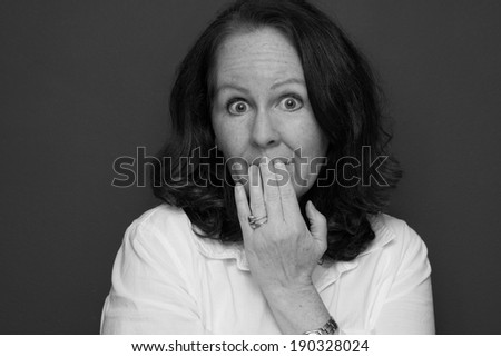 horizontal orientation close up in black and white of a single woman with her hand to her mouth and a look of embarrassment / Oops! - stock photo
