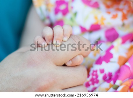 horizontal orientation close up of a baby girl's hand holding her father's hand with shallow depth of field / A Baby's Touch - stock photo