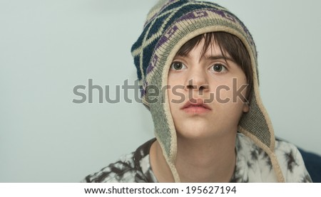 horizontal orientation close up of a boy with autism and down's syndrome wearing a wool winter hat with a neutral background and copy space / Winter Hat on a Teenager with Autism and Down's syndrome - stock photo