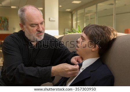 horizontal orientation close up of a father helping his son with disabilities put on a necktie / Father helping son with autism and Down's Syndrome with a necktie - stock photo