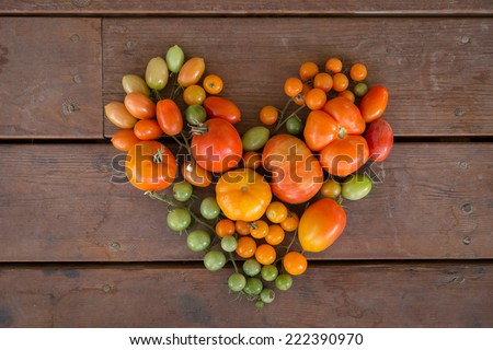 horizontal orientation close up of a variety of colorful tomatoes in the shape of a heart, on a neutral wooden background / Heart Healthy - Horizontal - stock photo