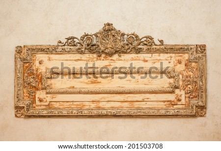 horizontal orientation close up of a weathered, vintage, wooden plaque with scrollwork in warm tones and neutral background, with copy space / Vintage Wooden Plaque - stock photo