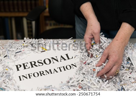 horizontal orientation close up of a woman's hands gathering shredded paper to recycle with the words PERSONAL INFORMATION shown / Protecting Personal Information - stock photo