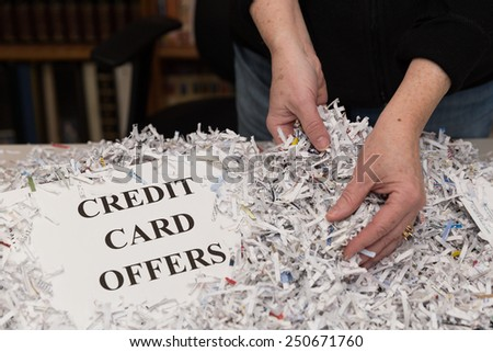 horizontal orientation close up of a woman's hands gathering shredded paper to recycle with the words CREDIT CARD OFFERS shown / Destroying Credit Card Offers - stock photo