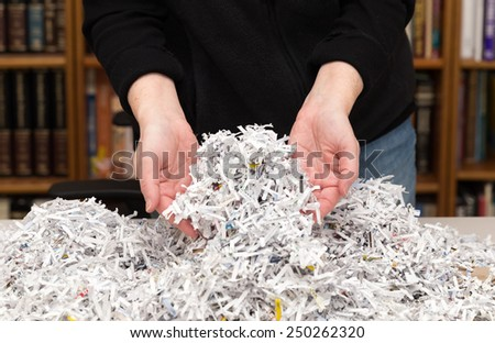 horizontal orientation close up of a woman's hands holding shredded paper in an office environment /  Hands Full of Shredded Documents - stock photo