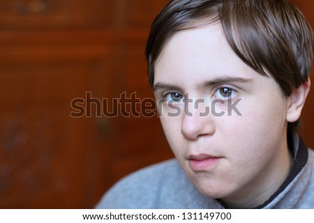 horizontal orientation close up of boy with autism and down's syndrome playing indoor with shallow depth of field and copy space / Autism affects almost Everyone - stock photo