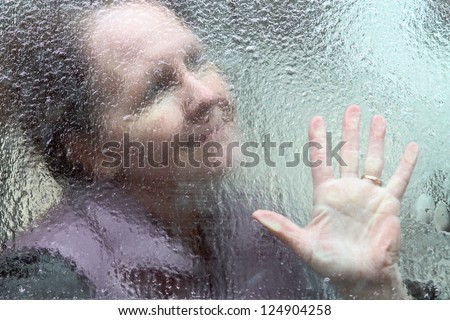 horizontal orientation close up outline of a smiling woman and her hand through a window covered in thick ice / Hope through the Winter - stock photo