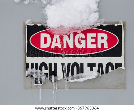 horizontal orientation color image of a Danger-High Voltage sticker, peeling, with icicles hanging from it, and copy space / Danger-High Voltage peeling Sticker with Icicles and Snow - stock photo