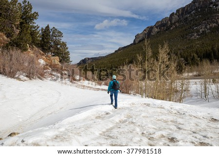horizontal orientation color image of a single woman hiker with backpack and crampons hiking through the snow in winter / Winter Recreation at Rocky Mountain National Park - stock photo