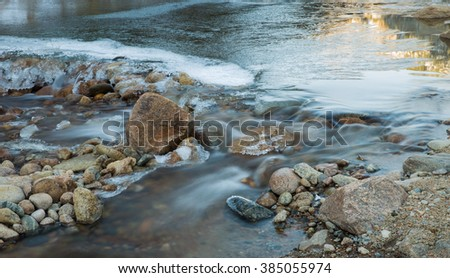 horizontal orientation color image, taken with a very slow shutter speed to show the movement of water in a partly frozen stream with rocks / Small waterfall in Winter