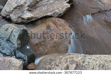horizontal orientation color image, taken with a very slow shutter speed, to show the movement of water along a rocky creek in Colorado / Winter Waterfall and Boulders