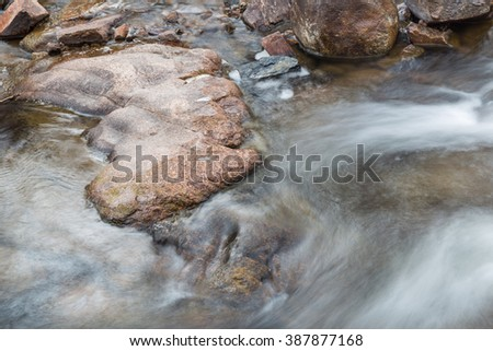 horizontal orientation color image, taken with a very slow shutter speed, to show the movement of water along a rocky creek in Colorado / Beautiful Winter Waterfall with Rocks - stock photo