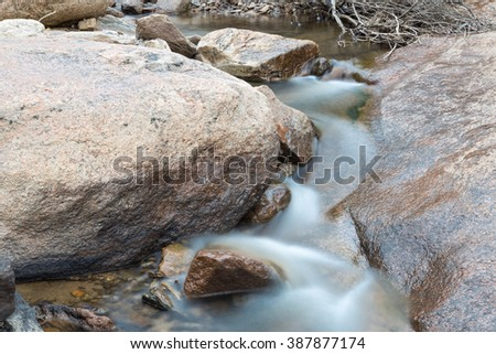 horizontal orientation color image, taken with a very slow shutter speed, to show the movement of water along a rocky creek in Colorado / Flowing Waterfall in Colorado - stock photo
