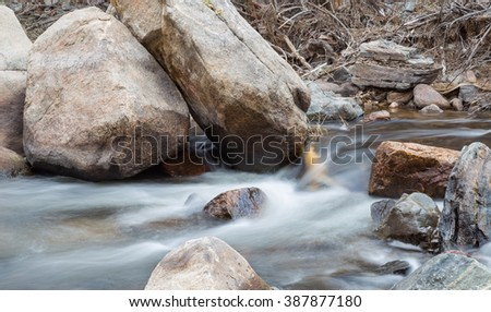 horizontal orientation color image, taken with a very slow shutter speed, to show the movement of water along a rocky creek in Colorado / Big Boulders and Creek in Winter - stock photo