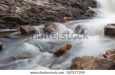 horizontal orientation color image, taken with a very slow shutter speed, to show the movement of water along a rocky creek in Colorado /  Beautiful, flowing Water - stock photo