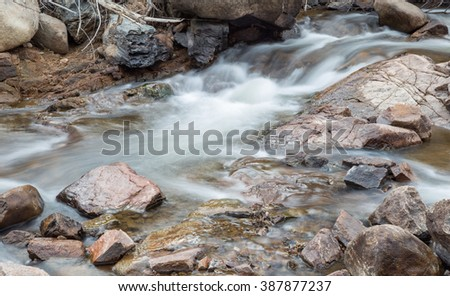 horizontal orientation color image, taken with a very slow shutter speed, to show the movement of water along a rocky creek in Colorado /  Hiking in Winter alongside a Rocky Creek