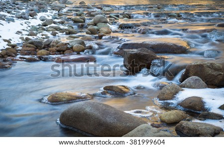 horizontal orientation color image, taken with slow shutter speed, to show water flowing over rocks with ice formations, in winter / Winter Scenery and Flowing Water - stock photo