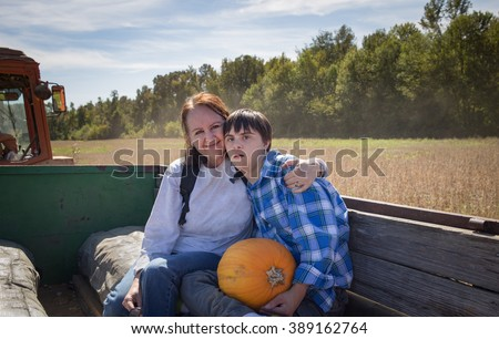 horizontal orientation color image with shallow depth of field, with a happy mother and her son with autism and down's syndrome on a hay ride / Choosing a pumpkin with Mom - stock photo