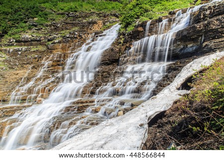 horizontal orientation color image with snow in the foreground and waterfalls with steep terrain in the background on a sunny day / Snow and Waterfalls in Glacier National Park, Montana USA