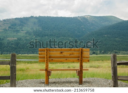 horizontal orientation of a single, empty, wooden bench in the foreground, with the majestic Selkirk Mountain Range in the background, and copy space / Spectacular Northern Idaho - Horizontal - stock photo