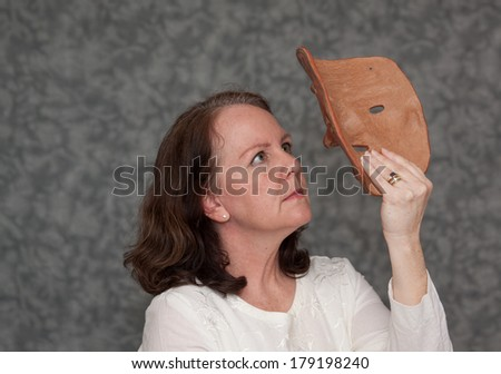 horizontal orientation of a single woman looking up at a clay mask with a serious look, neutral grey background and copy space / Facing Mental Illness - stock photo