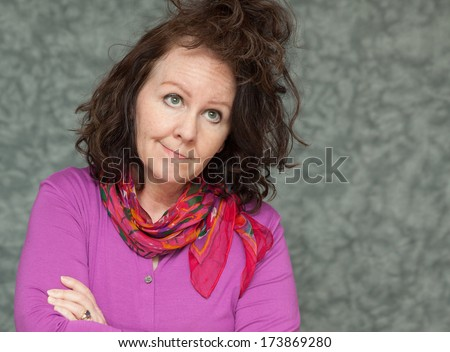 horizontal orientation of a woman in brightly colored business attire with a questioning look on her face and a crazy hair style with neutral background / Bad Hair Day - stock photo