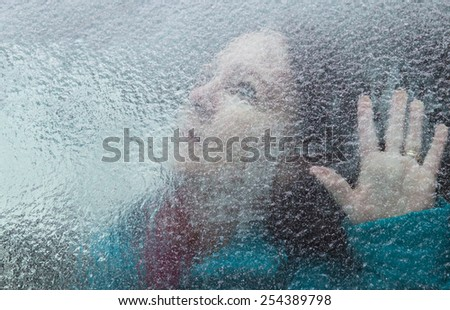 horizontal orientation of an attractive woman looking out through a window covered with thick ice, with her hand at the window / Memory Loss - stock photo