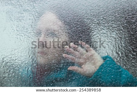 horizontal orientation of an attractive woman looking out through a window covered with thick ice, with her hand at the window / Signs of Alzheimers Disease - stock photo