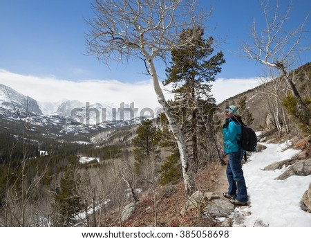 horizontal orientation with a happy woman hiker with a backpack and crampons looking out over a steep valley to snow covered mountains / Rocky Mountain overlook in Winter with Woman Hiker  - stock photo