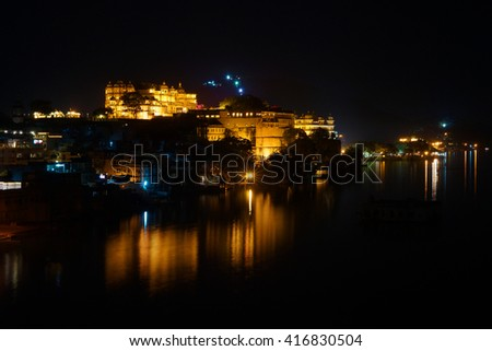 Horizontal panorama of the Udaipur City Palace and Pichola lake on the night with accent lighting, Rajasthan, India - stock photo