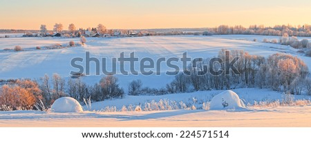 Horizontal panorama of winter snow-covered hills with village at sunset. - stock photo