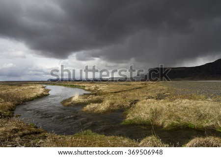 Horizontal panorama view of an Icelandic river running through the grass with rain stormy clouds above and mountains on the right side - stock photo