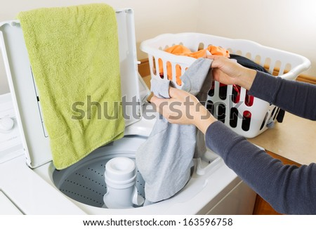 Horizontal photo female hands putting dirty laundry into washing machine   - stock photo