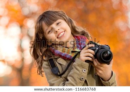 horizontal photo, happy beautiful little girl with photocamera, autumnal portrait - stock photo
