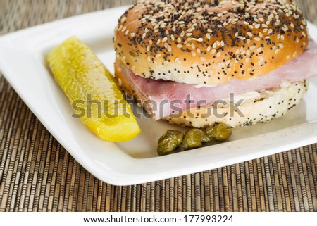 Horizontal photo of a ham sandwich with fresh sliced pickle and capers on white plate with bamboo mat underneath - stock photo