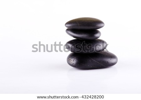 Horizontal photo of black lava stones. Black stones stacked at each other. Few stones on white board. Relaxing lava stones placed isolated on white background. - stock photo