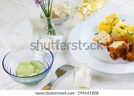Horizontal photo of breaded cauliflower with chive potatoes on white plate. Fork, salt, cucumber salad, tatar sauce dip, glass of water and bottle with oil are around on white cloth. - stock photo