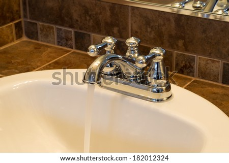 Horizontal photo of chrome faucet running water into bathroom sink with tile and partial mirror in background  - stock photo