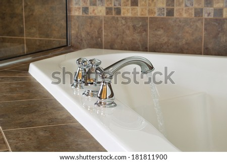 Horizontal photo of chrome faucet running water into soaking tub in master bathroom with partial shower glass in background  - stock photo