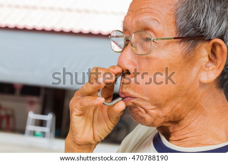horizontal photo of closeup thai old man using nasal Snuff pipe for relieving his nasal congestion