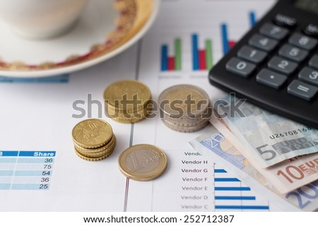 Horizontal photo of euro coins in stacks and bills under calculator with coffee cup in background placed on paper sheets with bar charts.