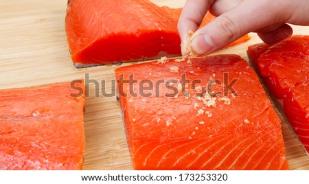 Horizontal photo of female fingers placing sea salt on fresh pieces of Wild Red Salmon and natural bamboo board in background  - stock photo