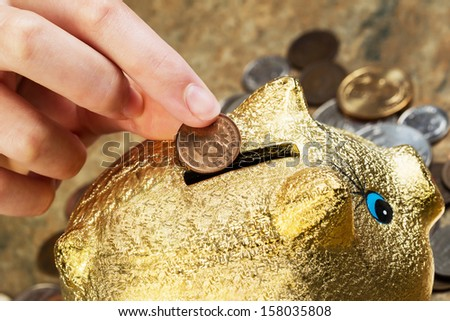 Horizontal photo of female fingers putting single cent into piggy bank with coins lying around on stone counter in background - stock photo