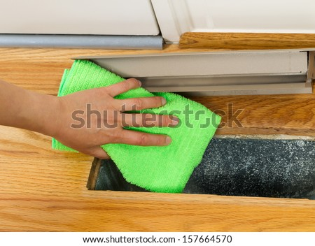 Horizontal photo of female hand cleaning, using microfiber rag, underneath grill plate of heater floor vent with Red Oak Floors and front door in background  - stock photo