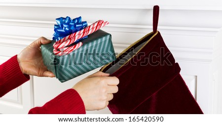Horizontal photo of female hands putting present and candy canes into Christmas stocking