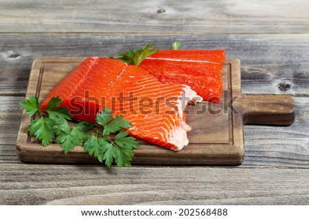 Horizontal photo of fresh raw red salmon fillet on traditional wooden server with parsley on the side and rustic wood underneath  - stock photo