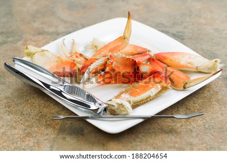 Horizontal photo of freshly cooked Dungeness crab legs, focus on large claw in center, on white plate with stainless crab crackers and stone counter top underneath   - stock photo